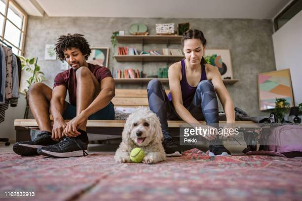 young multi-ethnic couple preparing for jogging - black shoe stock pictures, royalty-free photos & images