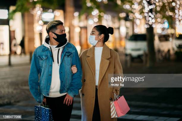 young multi-ethnic couple walking in street with shopping bags in city while wearing protective face masks for illness prevention in winter - coronavirus winter stock pictures, royalty-free photos & images
