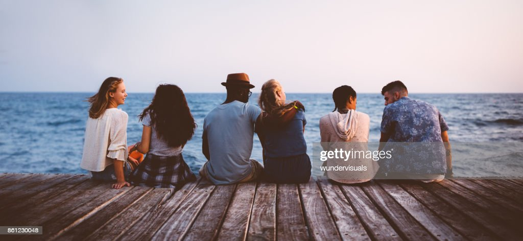 Young multi-ethnic couples and friends sitting on wooden jetty together : Stock Photo