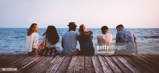 young multi-ethnic couples and friends sitting on wooden jetty together - pier stock pictures, royalty-free photos & images
