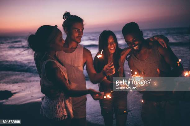 Young multi-ethnic couples celebrating with sparklers at beach after sunset