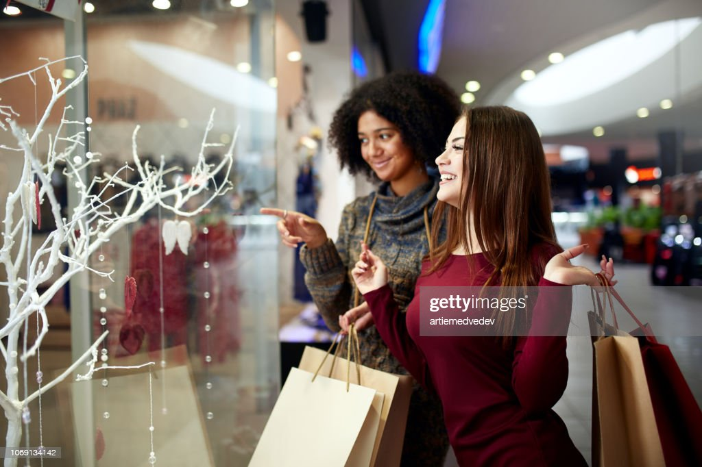 Young multiethnic diverse race women with paper shopping bags near decorated shopwindow. Girl pointing by finger at shopfront, clothes and products in mall on christmas new year sale. : Stock Photo