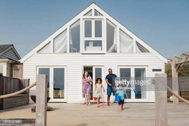 joven familia multiétnica caminando al aire libre en casa de playa - chalet veraniego fotografías e imágenes de stock