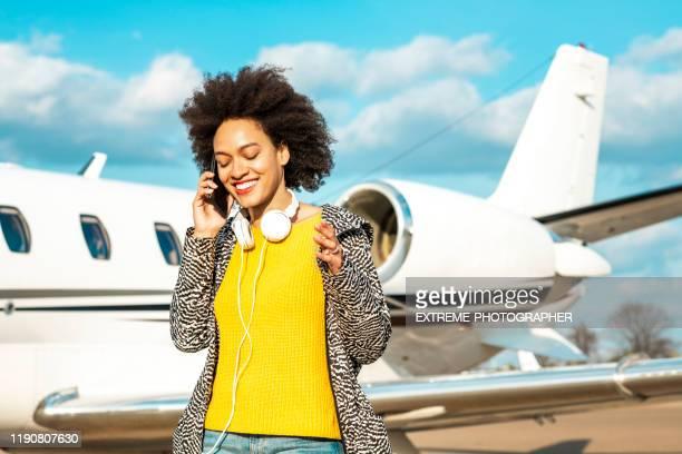 junge multiethnische unternehmerin spricht auf einem handy in der nähe eines privatflugzeugs - flugzeugheck stock-fotos und bilder