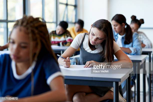 young multi-ethnic female students writing exam - vie scolaire photos et images de collection