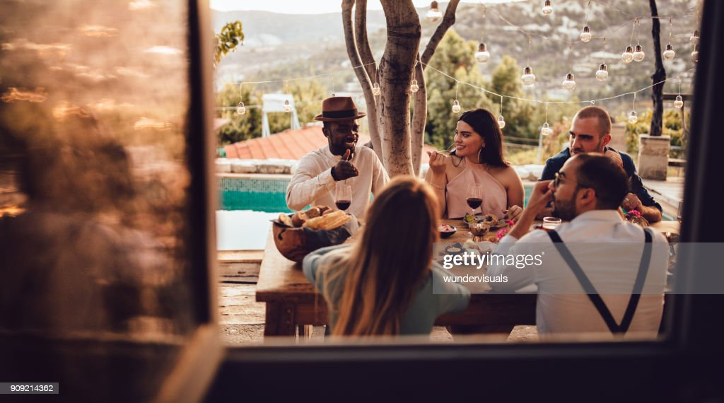Young multi-ethnic friends and couples having lunch at village house : Stock Photo