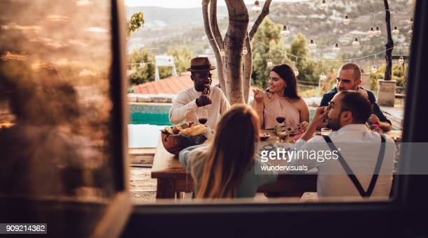 young multi-ethnic friends and couples having lunch at village house - vintage restaurant stock pictures, royalty-free photos & images