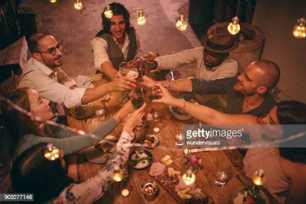 Young multi-ethnic friends celebrating and toasting at rustic dinner party
