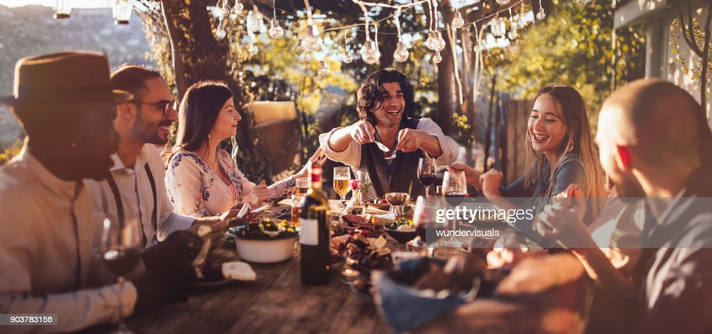 Young multi-ethnic friends dining at rustic countryside restaurant at sunset : Stock Photo