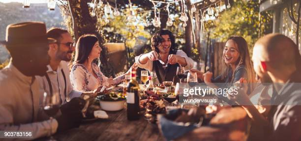 Young multi-ethnic friends dining at rustic countryside restaurant at sunset