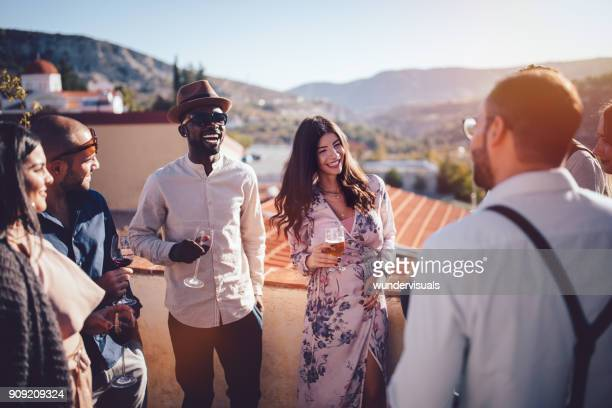 Young multi-ethnic friends drinking wine and beer in rustic village