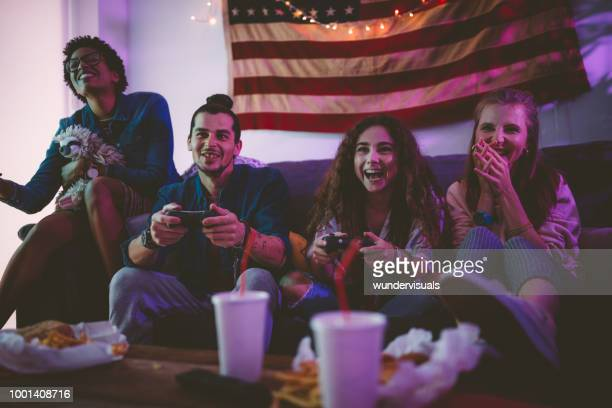 young multi-ethnic friends eating fast food and playing video games - room after party stock pictures, royalty-free photos & images