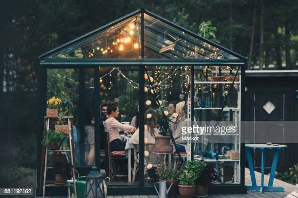 Young multi-ethnic friends enjoying dinner party in glass conservatory room at back yard