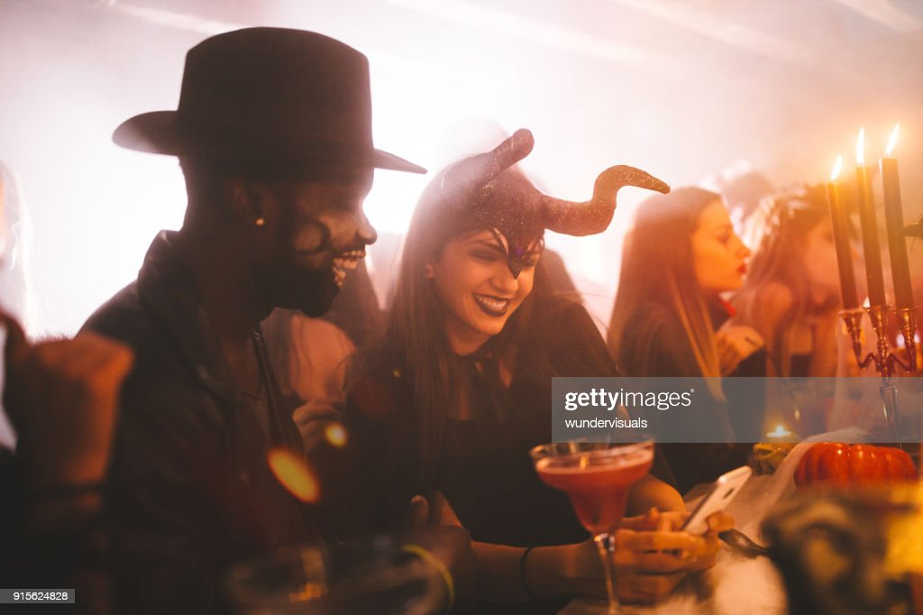 Young multi-ethnic friends in costumes texting at Halloween party : Stock Photo