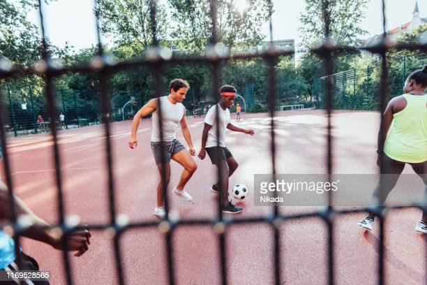 junge multiethnische freunde spielen fußball durch zaun gesehen - sportlicher zweikampf stock-fotos und bilder