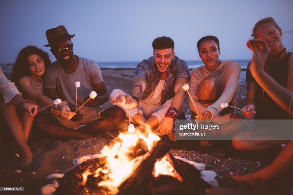 Multi-ethnischen Jugendliche Rösten Marshmallows auf Stöcken am Strand : Stock-Foto