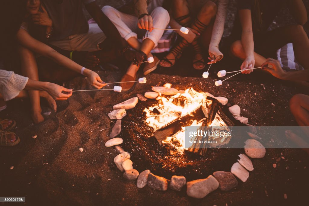 Young multi-ethnic friends roasting marshmallows over campfire at beach party : Stock Photo