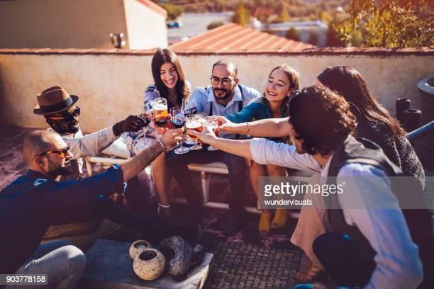 Multi-ethnischen Jugendliche Toasten mit Getränke an Land rustikales Landhaus