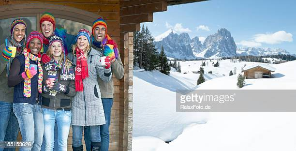 Young multi-ethnic group celebrating under cabin roof in snowy mountains