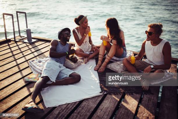 young multi-ethnic hipster friends and couples relaxing on jetty - juice drink stock photos and pictures