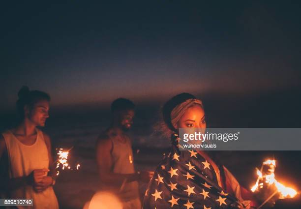Young multi-ethnic hipster friends celebrating fourth of July with sparklers