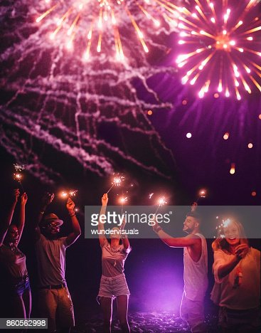 Young multi-ethnic hipster friends celebrating with sparklers and fireworks display