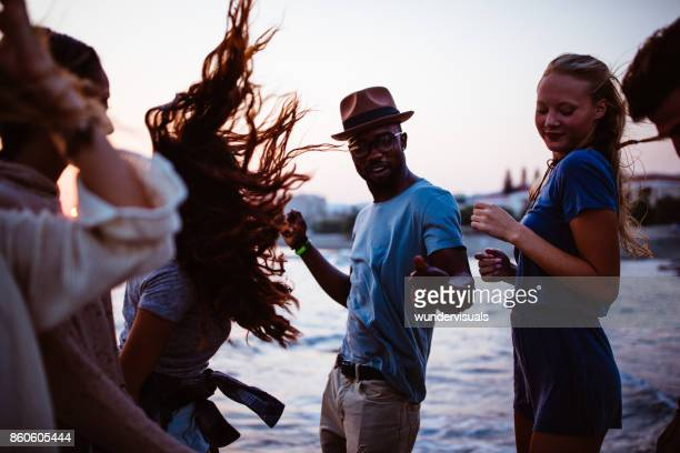 Young multi-ethnic hipster friends dancing at beach party at sunset