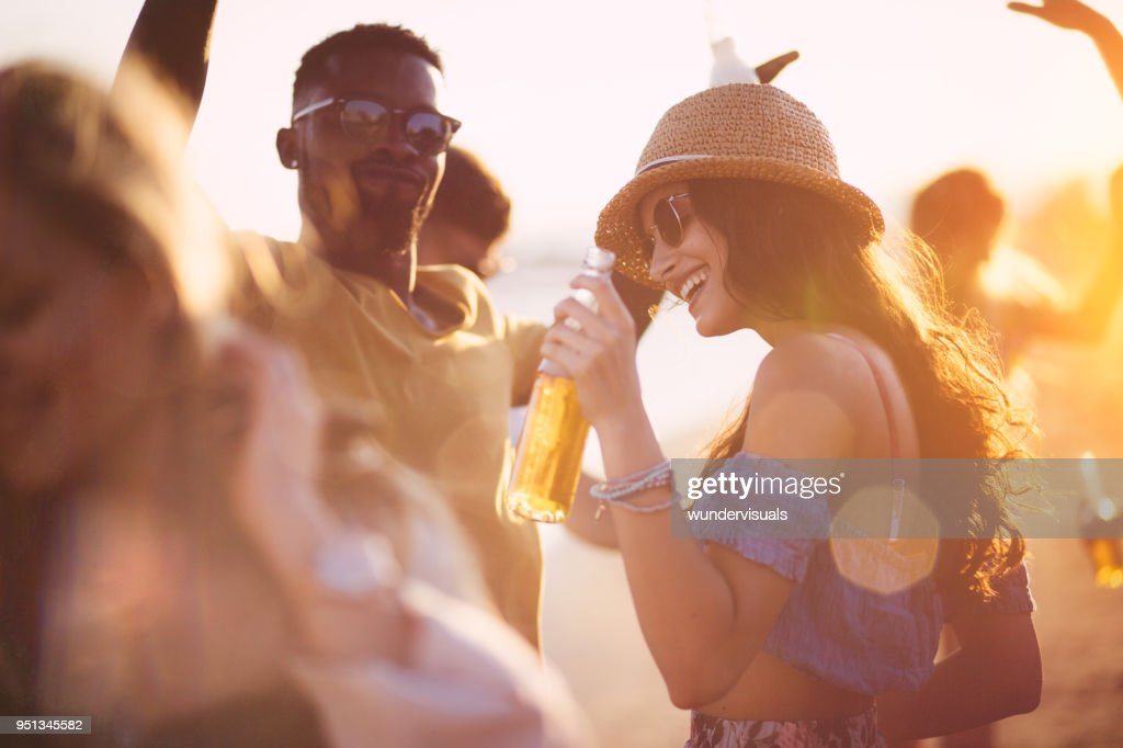 Young multi-ethnic hipster friends dancing at summer beach party : Stock Photo