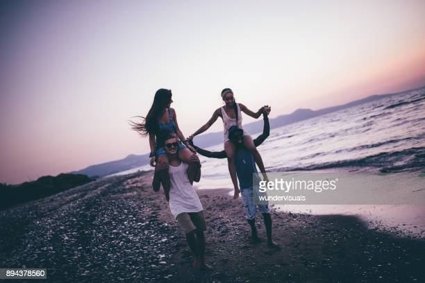 young multi-ethnic hipster friends having fun with beach piggy-back rides - carrying a person on shoulders stock photos and pictures