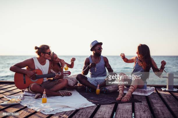 Young multi-ethnic hipster friends having party with guitar on jetty