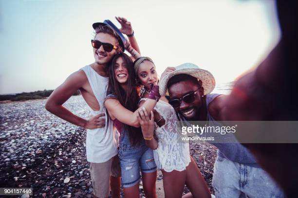 Young multi-ethnic hipster friends taking selfies on island summer vacation