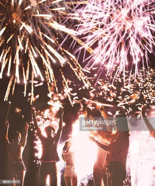 Gente joven inconformista multiétnica celebrando con bengalas y fuegos artificiales