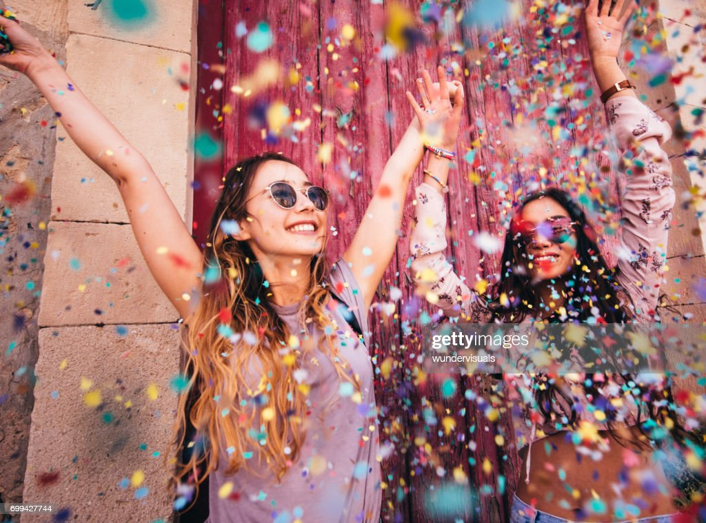 Young multi-ethnic hipster women celebrating with confetti in the city : Stock Photo
