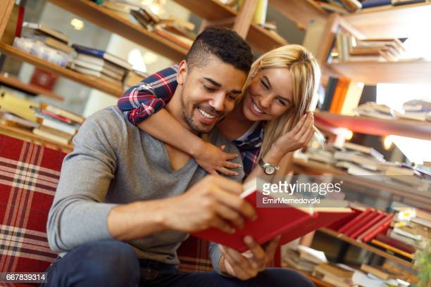 Young Multi-ethnic student couple enjoy  book reading in the library.