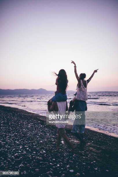 young multi-ethnic tourist friends giving piggy-back rides on island beach - carrying a person on shoulders stock photos and pictures