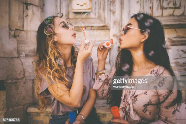 Young multi-ethnic women blowing bubbles in old city street