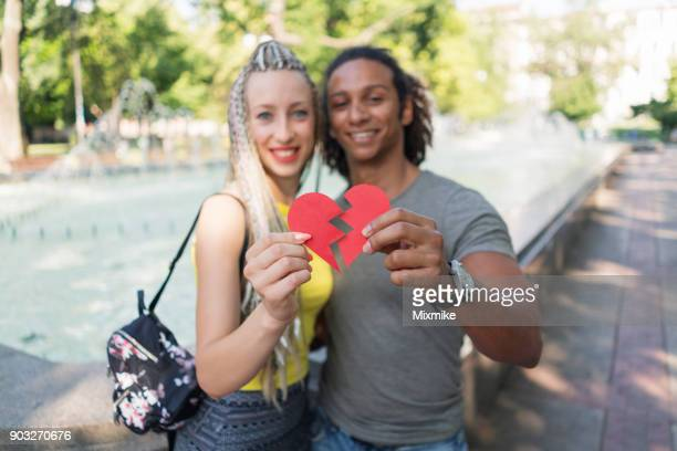 young multiracial couple embracing and joining together torn red heart - valentines african american stock pictures, royalty-free photos & images