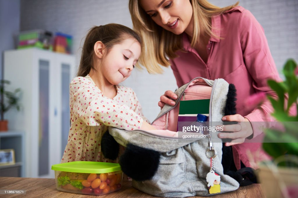 Young mum and daughter packing backpack for the school : Stock Photo