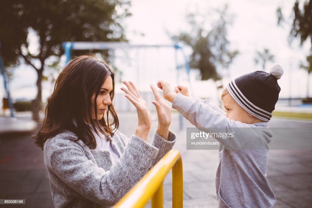 Young mum high fives excited baby boy at the playground : Stock Photo