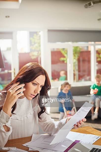 young mum queries a bill on the phone .