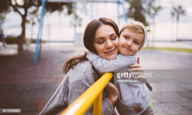 Young mum tenderly hugs young boy at the playground