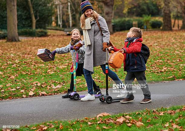 Young mum walking children from school in autumn