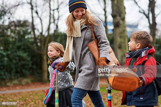 young mum walking her children from school - coat stock pictures, royalty-free photos & images