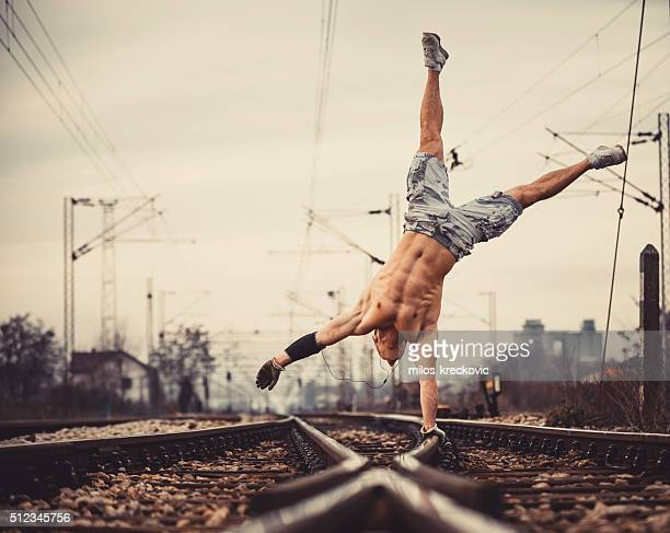 Young muscle man on railroad tracks