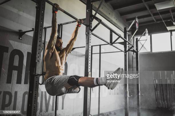 young muscular build athlete exercising strength in a gym. - chin ups stock photos and pictures