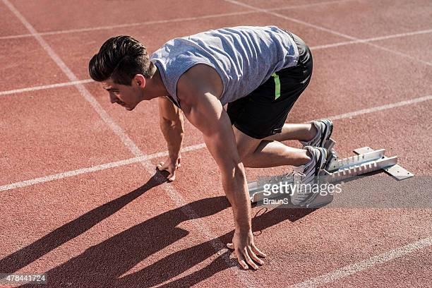 Junge Muskulös Sportler an der Startlinie.