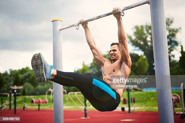 Young muscular build man exercising at outdoor gym.