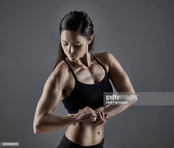 Young, muscular female tensing bicep