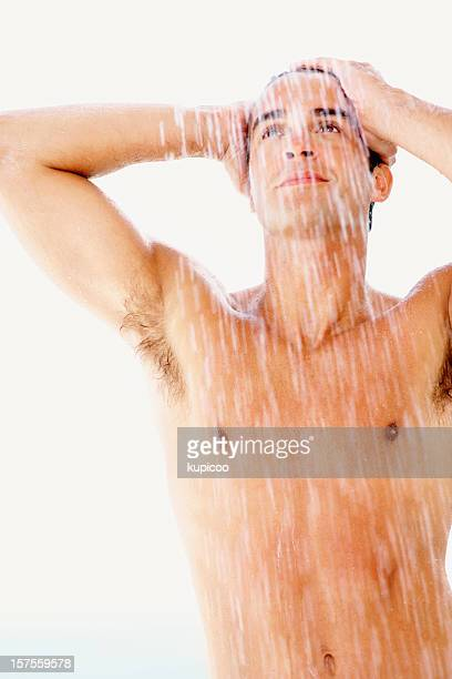 Young muscular guy with water raining down on him