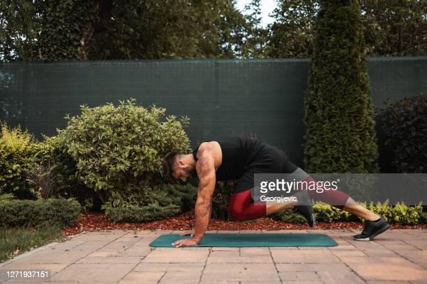 屋外で筋力運動をしている若い筋肉の男。 - 自重トレーニング ストックフォトと画像